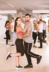 Dancing couples learning salsa at dance class