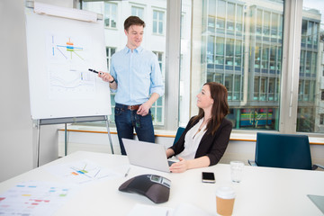 Businessman Giving Presentation To Coworker In Office