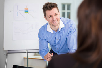Smiling Businessman Looking At Female Colleague In Office