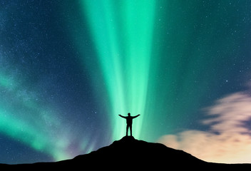 Aurora and silhouette of standing man with raised up arms on the mountain. Lofoten islands, Norway. Aurora borealis and happy man. Sky with stars and green polar lights. Night landscape with aurora