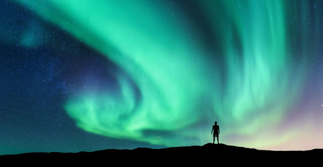 Foto op Plexiglas Groene koraal Aurora borealis and silhouette of standing man. Lofoten islands, Norway. Aurora and happy man. Sky with stars and green polar lights. Night landscape with aurora and people. Concept. Nature background