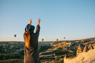 A tourist girl in a hat admires hot air balloons flying in the sky over Cappadocia in Turkey. Impressive sight.