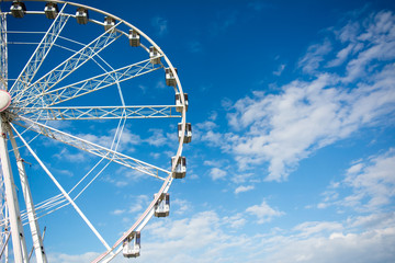 Horizontal View of a White Ferris Wheel on Partially Cloudy Sky Background. Copy Space. Bari, South of Italy