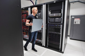 Computer Engineer Carrying Blade Server While Walking In Datacen