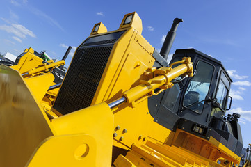 Bulldozer, row of huge yellow powerful construction machines with big scoop and tracks, heavy industry, bottom view, blue sky and white clouds on background