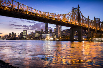 The lights of New York City and the Queensboro Bridge reflect off the water of the East River as the sun sets over the city.