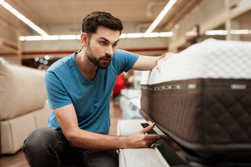 Handsome bearded man is testing mattress in furniture store. Orthopedic mattress for a healthy posture.