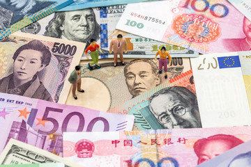 mini people are on banknotes of different countries