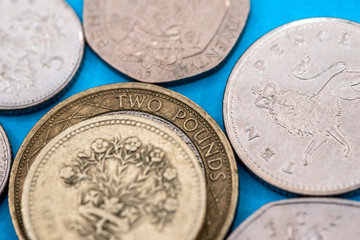 Different Pound coins on a blue background.