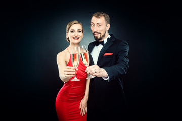 Elegant woman and man clinking glasses on glamourous party wearing formal dinner jacket and evening dress