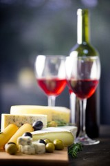 Wine Bottle, Wine Glasses, Olives and Cheeses on the Wooden
