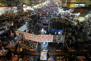 "People shop at Al Ataba, a popular market, near a campaign poster of Egypt's President Abdel Fattah al-Sisi, that reads: ""All of us with you"", in Cairo"