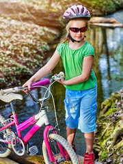 Bicycle children with ladies bikes in summer park. Child road bike for running on nature. Kid girl in helmet cycling fording throught water. Cycling trip is good for health outdoor. School trip.