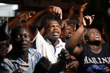 People gesture as they show their support for the ruling All Peoples Congress (APC) party outside the party's headquarters in Freetown