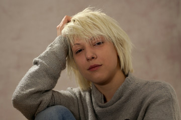 Young blonde girl portrait in a casual mood. She's looking at camera with a friendly gesture.