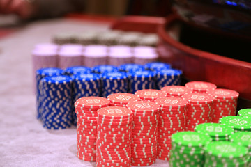 Poker chips colorful gaming pieces lie on the game table in the stack