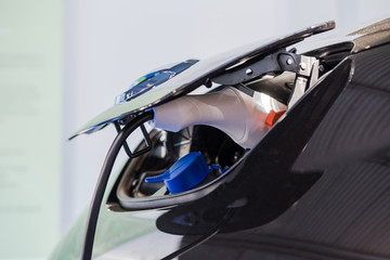 Close up of the Hybrid car electric charger station with power supply plugged into an electric car being charged.