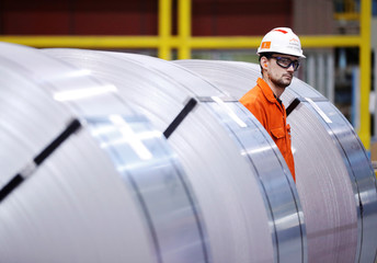 A worker looks at rolls of steel at the ArcelorMittal Dofasco steel plant in Hamilton