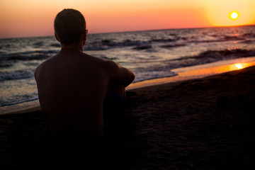 silhouette of a man who sits on the sand near the sea, in the rays of the setting sun near the sea. place under the text, relax on the sea