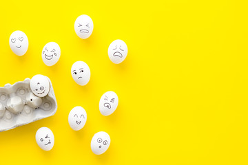 Emotions in communication at social media. Faces drawn on eggs. Happy, smile, sad, angry, in love, saticfied, laughing. Yellow background top view copy space
