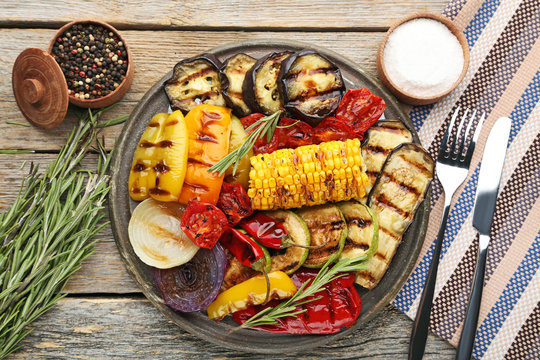 Grilled vegetable on brown cutting board with rosemary, salt and pepper