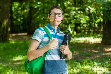 Photo of student with pencil in mouth, glasses