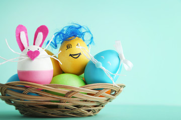 Eggs with funny faces in basket on mint background