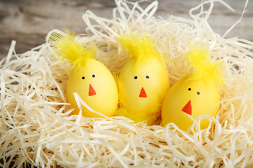 Yellow eggs with funny chicken faces in nest