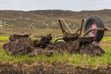 Inverasdale, Scotland - June 9, 2012: Closeup of turned over rusty wheel barrel at peat digging site. Green grass as background.