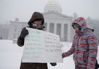 Kelly McCracken holds a sign as she looks over at her 14 year old daughter Edie Donofrio as they attend an anti-gun vigil outside the Vermont State Legislature in Montpelier
