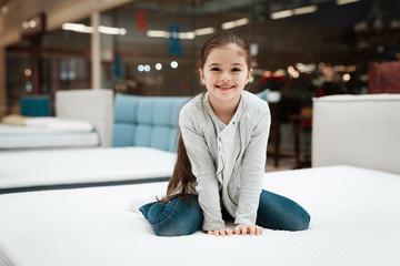 Happy little girl sitting on mattress in mattress store. Choosing mattress in store.
