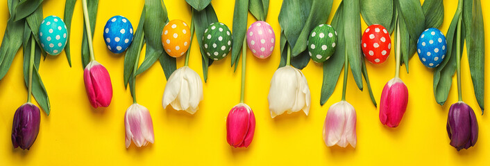 Easter eggs with colorful tulips on yellow background. Easter holiday concept.