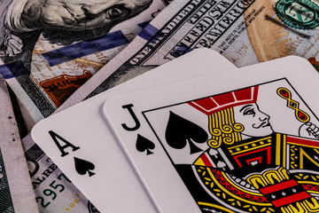 Closeup of a Blackjack 21 hand on a bed of one hundred dollar bills I