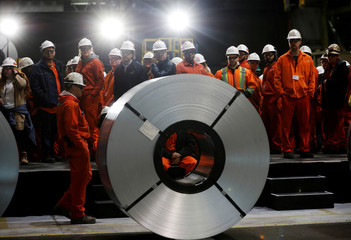 Workers stand behind rolls of steel at the ArcelorMittal Dofasco steel plant in Hamilton