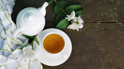 Hot green tea in a teapot and cup with a branch of jasmine flowers blossom  and white towel on rough rustic brown wooden background. Top view, nature healthy slow life concept.