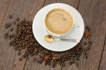 A Cup of coffee and coffee beans on wooden table.