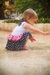 Cute Adorable Two Years Old Toddler Girl with Blonde Hair and Big Blue Eyes in Summer Dress with American Flag Print  is Dancing at the Rain, by the Pool Area in Cancun Resort in Mexico, March 2018