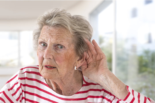 Elderly lady with hearing problems due to ageing holding her hand to her ear as she struggles to hear, profile view on large windows background