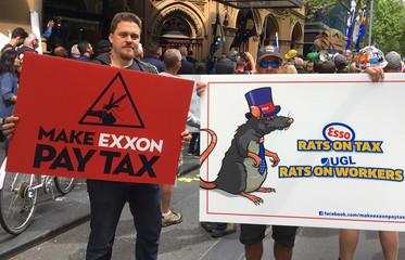 Protesters against ExxonMobil Corp carry banners and chant slogans as they march to the venue of an Australian Senate inquiry into corporate tax avoidance in central Melbourne