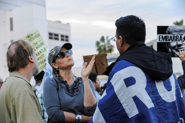 Melanie Chapman talks with Danny Rodriguez at protest at an anti-Trump protest in a park a few miles from a gated community where U.S. President Donald Trump is holding a fundraiser in Beverly Hills