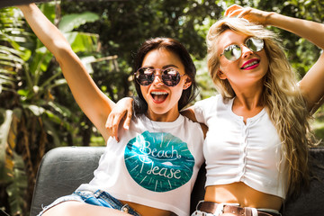 two girls best friends travel on a tropical island in a car with an open top are having fun having a smile. enjoyment travel, excursion summer dressed shorts T-shirts sunglasses
