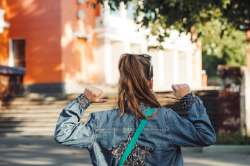 Cheerful little girl in jeans clothes with star on her back against blurred city landscape.