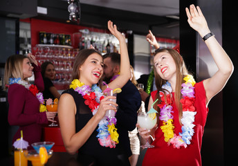 Female colleagues on company party in Hawaiian style in bar