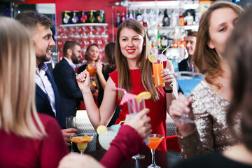 Woman with colleagues enjoying corporate party in bar
