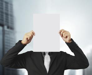 Hand holding white blank paper sheet