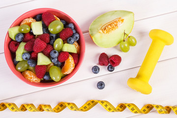Fresh fruit salad and tape measure with dumbbells, healthy lifestyle and nutrition concept