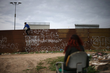 Alexis, 22, laborer, looks on near prototypes of President Donald Trump's border wall with Mexico, behind the current border fence in this picture taken from the Mexican side of the border in Tijuana
