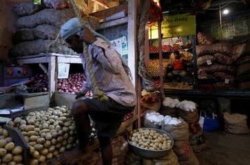 A vendor climbs to his stall as another waits for customers at a wholesale vegetable market in Mumbai