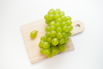 Green grapes on chopping board isolated on white background