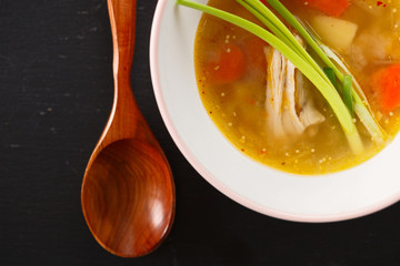 homemade chicken soup in white plate on black background